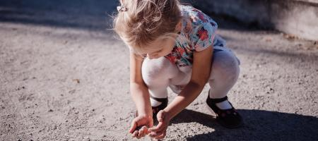 Neglected little girl playing in dirt